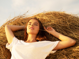 Calm Young woman is relaxing   on the haystack.