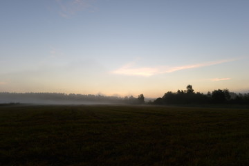 Sunlight of dawn in the blue sky above a field in the morning mist early morning.