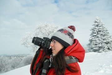 Young beautiful woman in a bright red jacket and hat photographs the winter landscape on top of the mountain. Close-up photo
