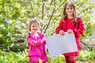 Two smiling sisters stand near the apple tree and hold a white sheet of paper. Springtime in the countryside.