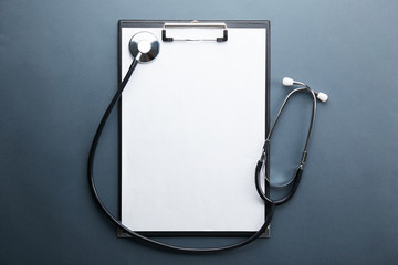 Doctor's working table with stethoscope acoustic medical device, eyeglasses and pen, blank medical record chart or test results on clipboard. Close up, copy space, background, top view, flat lay. Wall mural