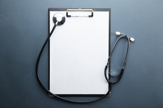 Doctor's working table with stethoscope acoustic medical device, eyeglasses and pen, blank medical record chart or test results on clipboard. Close up, copy space, background, top view, flat lay.
