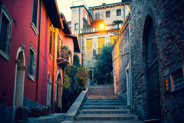Narrow little street with stairs in Verona, Italy red and orange walls of buildings and wooden windows. City street with old architecture and green flowers. Evening mysterious lights.