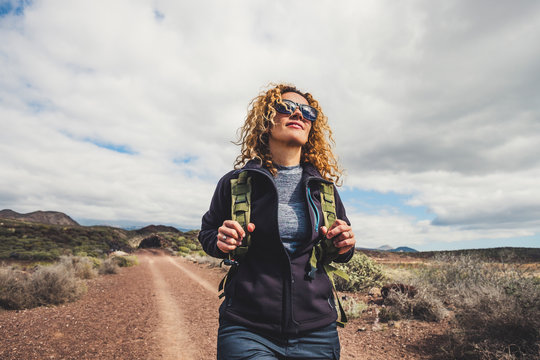 Young beautiful woman with backpack and trekking hiking in the mountains. Concept healthy and active lifestyle. Female on nature background with rocky background . adventure travel leisure activity