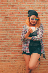 Happy young hipster woman standing against brick wall in town street with coffee cup in her hand.