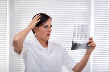 Dentist Looking At Tooth's X-ray Holding Hand