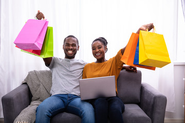 Happy Couple With Laptop Holding Colorful Shopping Bags