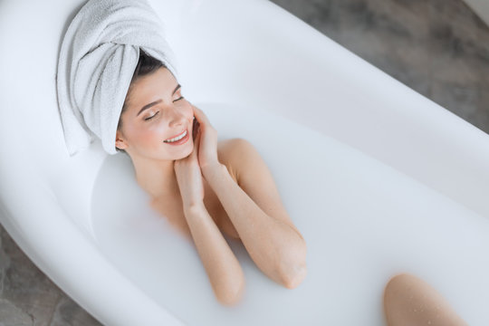 Gorgeous young brown-haired woman taking a relaxing milky bath, touching her clean fresh skin face and closes her eyes from bliss in a relaxing atmosphere.