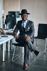 black man wears fashion hat, suit sitting on the office chair and looking at the camera . full length photo. free time