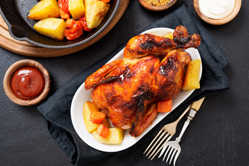 Roasted chicken with vegetables served  with sauces on dark table, top view.