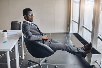serious business man is resting in the chair after the meeting. side view full length photo. leader making up a plan at workplace