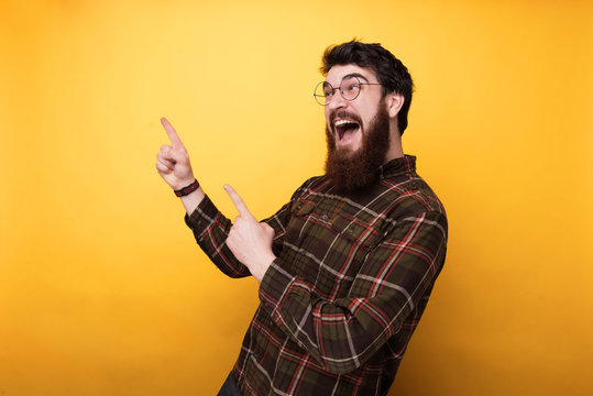 Portrait of excited bearded man inlooking an pointing at copy space over yellow background