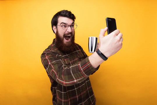 Portrait of Energized bearded man taking selfie while drinking coffee