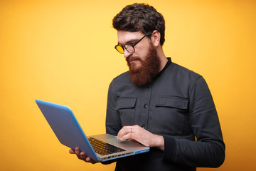Bearded man with laptop. Concentrated young busnssman in gray shirt using laptop over yellow background