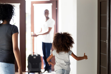 Happy child daughter running to meet african dad coming home with suitcase, rear view at little kid girl hurrying to hug father arriving after business trip, welcome back daddy, black family reunion