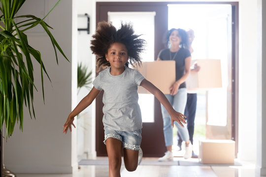 Happy cute black child girl running looking at camera exploring new house moving in, parents holding boxes entering new home with excited kid jumping in hallway, african family mortgage relocation