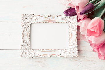 Photo frame and bouquet of fresh tulips on a light background