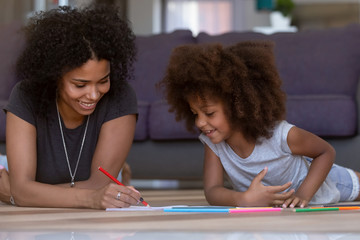 Happy mixed race single mom and cute kid daughter draw with colored pencil on warm floor together, african mother baby sitter helping teaching child girl play have fun at home, creative family hobby