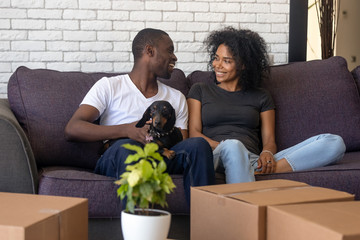 Young african american couple happy to move into new home with pet and boxes, black family tenants celebrate relocation sitting on couch with dog, homeowners renters having fun unpacking in own house