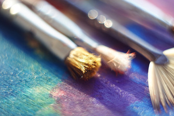 A synthetic brush, a brush with bristles and a fan brush lie on the palette, painted with different colors of oil