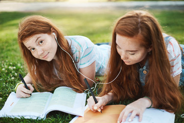 You wanted something to ask. Portrait of charming carefree redhead girl lying on grass in park with stister, sharing earphones while listening music to focus and doing homework together