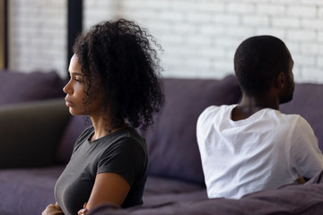 Sad unhappy african wife avoiding talk ignoring husband after couple fight feels indifferent offended, upset frustrated black girlfriend tired of problems, thinking of divorce with selfish boyfriend