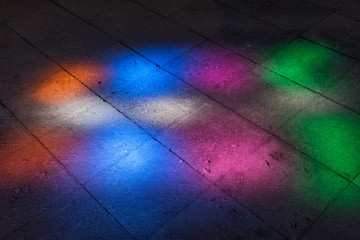 Colorful light spots on the floor. Sunlight filtered through the stained glass window