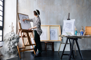 Modern young freelancer artist sculptor woman in headphone creates new art masterpiece drawing sketch at art workshop workplace studio exhibition with drawings, sketches and gypsum plaster sculptures.
