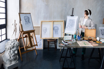 Modern freelancer artist sculptor woman in headphone creates new art masterpiece with cup of coffee at art workshop workplace studio exhibition with drawings, sketches and gypsum plaster sculptures.