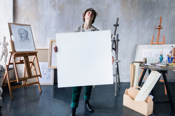 Young beautiful smiling artist teacher student woman girl boy in modern art workshop studio surrounded by black white sketch painting big easel tools hold huge art canvas for new artistic masterpiece