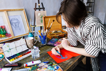 Pensive woman artist is drawing sketch with pastels on orange sheet of paper in art studio. Creative workplace on table with drawing tools, brushes, pastels, tubes, watercolors, palette. Art concept.