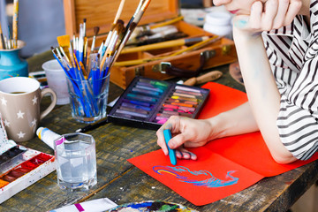 Pensive woman artist is drawing sketch with pastels on orange sheet of paper in workshop. Creative workplace on table with drawing tools, brushes, pastels, tubes, watercolors, palette. Art concept.