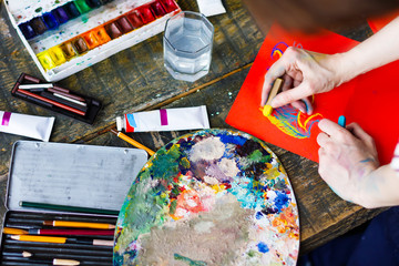 Soiled artists hands is painting on orange paper sheet. Top view of creative workplace on old wooden table with different drawing tools, paintbrushes, watercolors, pastels, tubes, palette. Art concept