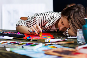 Young woman artist is falling asleep while draw sketch in her workshop. Closeup of creative workplace on wooden table with drawing tools, pencils, pastels, tubes, watercolors. Art concept.