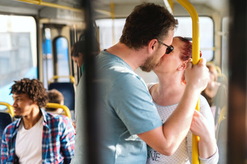 Caucasian married couple standing in the public transport and kissing. In background people sitting and standing.