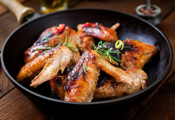 Baked chicken wings in pan on wooden table. Top View