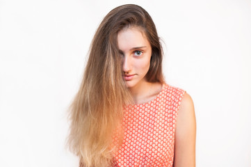 A beautiful girl with long, bright hair in a summer dress on a light background. The girl has an interesting, naughty look
