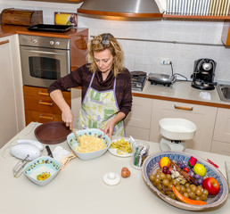 Housewife prepares an apple dessert in a messy kitchen