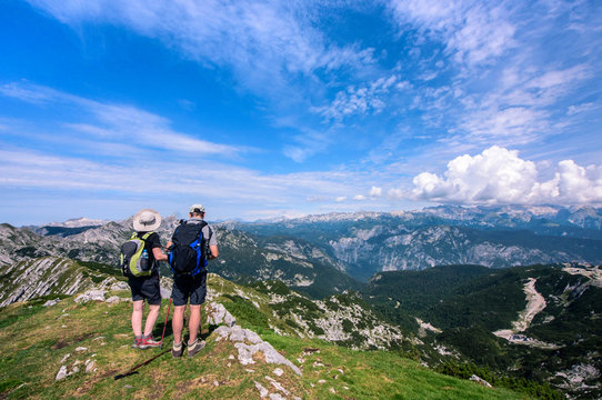 Rear view of man and woman in middle age with backpack hiking in beautiful mountain panorama, Slovenia