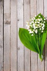 Wall Murals Lily of the valley bouquet of lily of the valley on old weathered wooden table background