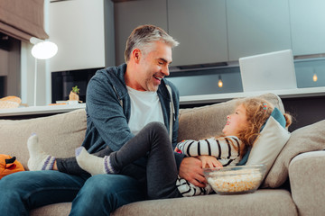 Adorable small long-haired girl and her father laughing happily