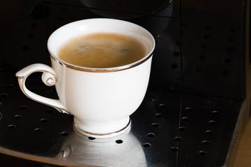 Obraz biała filiżanka kawy na podstawce ekspresu  - fototapety do salonu