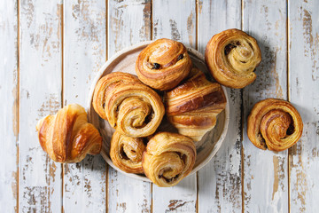 Variety of homemade puff pastry buns cinnamon rolls and croissant in ceramic plate over white plank wooden background. Flat lay, space Fototapete