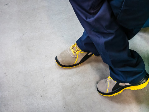 top view of the safety shoes worn by a worker on the industrial floor