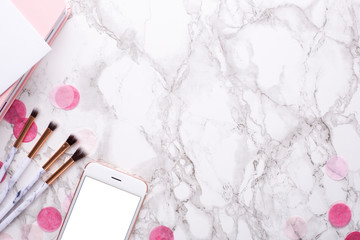 Cosmetic brushes and mobile phone on a marble background