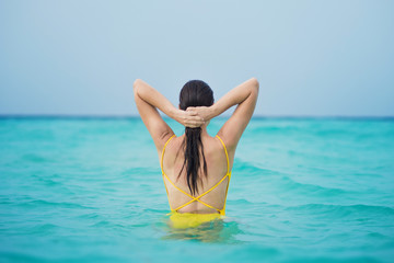 Young brunette woman in yellow one piece swimsuit.