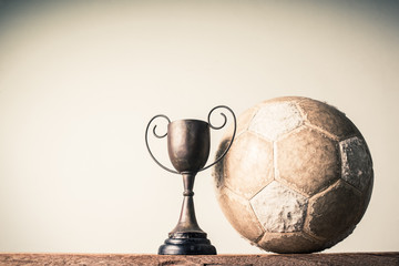 still life photography : old football and vintage trophy on old wood table in championship concept