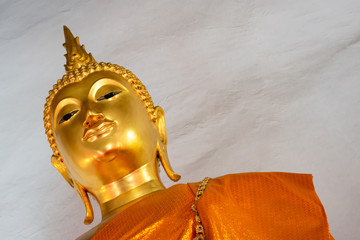 Up rise and tilt angle of golden buddha image .statue with space of rough concrete wall