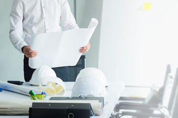 Business engineering man looking project constructed paper blueprint plans.