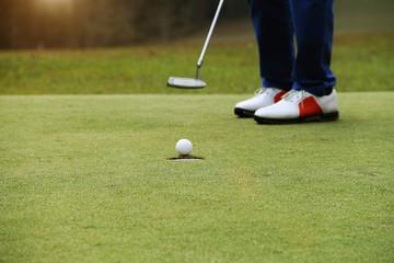 Golfer putting golf ball on the green golf